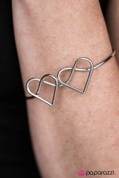 A glistening silver bar bends into two hearts across the wrist, creating a dainty cuff. The whimsical wire display allows the skin to peek beneath the crisscrossing heart silhouettes for an airy finish.    Sold as one individual bracelet.