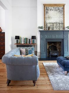 Glamorous traditional-styled living room with slate gray painted fireplace with antique gold mirror, light blue chesterfield sofa, tufted blue velvet cocktail ottoman and light gray Persian area rug.