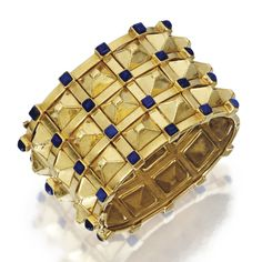 18 KARAT GOLD AND LAPIS LAZULI BANGLE-BRACELET    The wide sculptural hinged bracelet composed of polished gold pyramids, accented by lapis lazuli cabochons, gross weight approximately 104 dwts., internal circumference 7¼ inches, one lapis lazuli missing. Tiffany, probably. Why? Because this one is! http://www.sothebys.com/en/auctions/ecatalogue/2011/important-jewels/lot.185.html