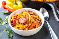 Flavor abounds in a sizzling skillet of smoked sausage and red rice with charred onions and peppers!