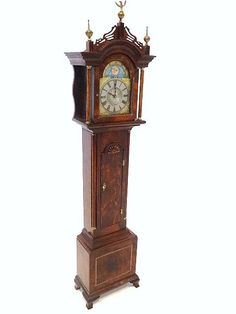 """Ernie Levy Tall Case Clock  A very fine flamed mahogany grandfather clock with tombstone door decorated with shell-carving, the base sporting a diagonally striped inlay, reeded column and quarter columns, and delicately carved fretwork cornice surmounted by brass finials. 8"""" at top of finial."""