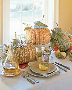 """The stippled skins of these """"One Too Many"""" pumpkins are adorned with marbleized Florentine-paper leaves and millinery-wire tendrils. Mini """"White Ball"""" gourds nestle at their feet, while """"Baby Boo"""" pumpkins find a spot at the table as place markers.Because none of the pumpkins in this subtly colored centerpiece are carved, they can last well into the fall, perhaps even until Thanksgiving.Print the Leaf Template"""
