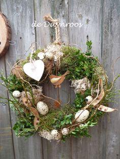 Voorjaarskrans Een grote krans (40 cm) in de vorm van een ei gedecoreerd met allerlei droge materialen, eitjes en buxus met een mandje voor bolletjes.Een haantje maakt de krans compleet.