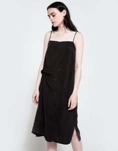 From Objects Without Meaning, a minimalist dress in Black. Features thin straps, twisted knot detail, interior lining, straight hem with split side seams and a classic fit.  • Dress in Black • Thin straps • Twisted knot detail • Interior lining • St