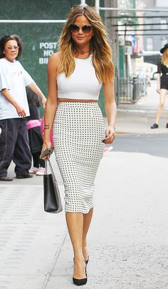 Chrissy Teigen in a polka dot skirt, white crop top, and black heels