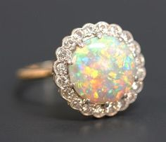 A gold, platinum, opal and diamond circular cluster ring, claw set with the circular opal within a