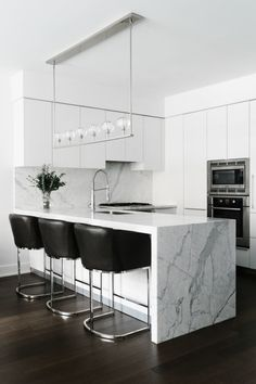 A marble island with contemporary black leather chairs make this all white kitchen come to life.
