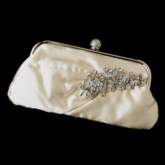 "The bridal satin crystal evening bag has a sparkling sprig brooch featuring crystalline leaves. From stem to tip this silver plated crystal encrusted brooch will add a dazzling touch to any ensemble.    Size: Bag - 9 1/2"" (Length) 5"" (Height) 1"" (Width)    Brooch - 4.25"" x 1.25""."