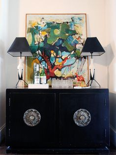 Hollywood glamour reigns in the entryway of this eclectic home. Vintage lamps sit atop a midcentury cabinet that doubles as a bar while the vintage painting anchors the area. Vintage Hollywood, Hollywood Glamour, Mid Century Cabinet, Vintage Lamps, Portfolio Design, Interior And Exterior, Exterior Design, Home Art, Home Accessories