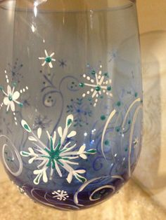 Hand painted blue wine glass with swirls and snowflakes and glitter accents. Heat cured, enamel paints, hand wash.