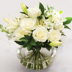 white centerpiece - no lilies, but roses, carnations, hydrangea, etc.. small vases to go inside wreaths