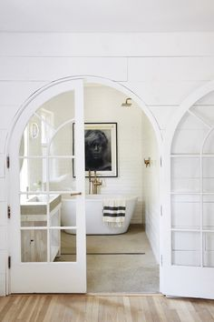 The most perfect modern farmhouse style bright white bathroom! I absolutely love these gorgeous French doors and that bathtub with the gold/bronze faucet.