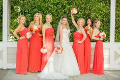Coral Ted Baker bridesmaid dresses with teal necklaces for a beach wedding.