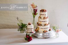 Wedding cake accompanied by flowers.
