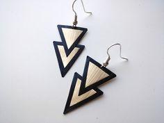 Les boucles d'oreille sont fabriquées à partir de capsule de café Nespresso recyclées. Elles sont composées de deux triangles superposés, un noir et un d'un doré. Les cap - 15620375