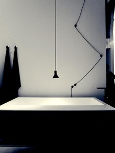 Vasca da bagno nera con lampada sospesa. Agape Design