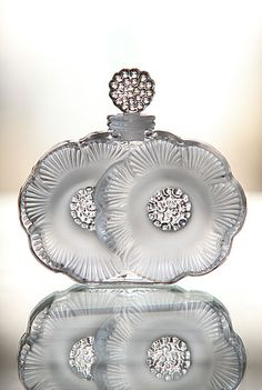 Lalique Two Flowers Perfume Bottle  Adorned by the Lalique coveted satin finish, this delicate perfume bottle is fashioned out of two blossoming flowers.