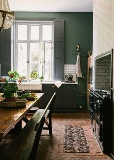 Deep green walls in an English country kitchen by deVOL kitchens.