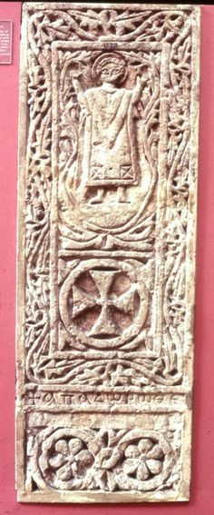 Limestone stela decorated with a representation of a figure with raised arms within a palm-wreath; cross in a circle below; foliate border; ...