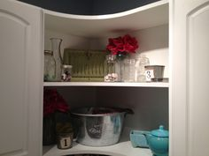 corner shelving in laundry room.  big tin bucket holds miscellaneous stuff while the rest is just to add color to the room.  I used an antique heating grate (green) to add color and texture to the top shelf then filled in with a variety of mason jars filled with sea glass and shells that I collected on vacations.  The pink flowers are just girly and fun...because seriously, I'm the only one who spends time in the laundry room, so I should be the one who loves it the most!