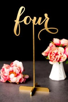 gold table number in cursive calligraphy on high stand