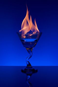 Continuing the flaming martini project from yesterday. This time, I bought a mirror to put the glass on. SB-600 with blue gel behind and underneath the glass pointed up at white background, triggered by pop-up flash, with a piece a white paper taped in front of it to prevent the pop-up flash from reflecting on the martini glass Nikon D90 with 50mm f/1.8 lens @ f7.1, ISO200, 1/320 (The flames were much brighter than I expected)