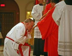 Venerate   The man is bowing in respect for someone