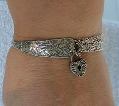 This is a bracelet I designed using a beautiful vintage 1885 sterling Gorham Saint Cloud spoon and a vintage early 1900s F&B Heart Key Lock. The lock is workable if you have a key. It has 9 sterling silver chain strands and a heavy sterling silver ornate toggle clasp. I removed the bowl off of the spoon and added the 9 strands of sterling chain. I was able to leave the makers mark, date, and sterling mark. I soldered all jump rings closed so a solid piece. The spoon face measures 1/2 across…