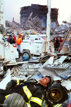 A New York City firefighter sleeps after an all-night shift at ground zero of the World Trade Center September 13. 2001 in New York City, two days after the twin towers were destroyed when two hit by two hijacked passenger jets.