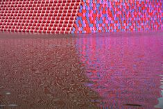 Christo's The London Mastaba at the Serpentine - The London Mastaba will float on the Serpentine Lake in Hyde Park – freely viewable by the general public – until 23 September 2018. Light reflecting many colors onto the water the scene is vibrant.