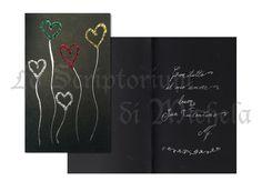 Biglietto su cartoncino nero. Decorazione esterna con inchiostro argento e cuori in glitter policromi. Testo interno in corsivo inglese color argento. Dim. 10,5x17 cm