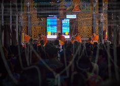 Songkran Ceremony in a Buddhist temple with sacred thread strung between the rafters and congregation.  Monk Blessed String Bracelets in Thailand (Sai Sin Sacred Thread). String blessed by monks to bring good luck and protection. Traditions and Culture in rural Thailand (Isaan) by http://potatoinrice.com/