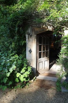 vines over French doors give way to a  beautiful garden hideaway