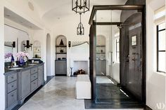Lanterns by Dennis & Leen hang from the vaulted ceiling in the Los Angeles bath of supermodel Gisele Bündchen and New England Patriots quarterback Tom Brady. A photograph of Gillette Stadium (where the Patriots play), by Jon Coulthard, hangs above the fireplace.