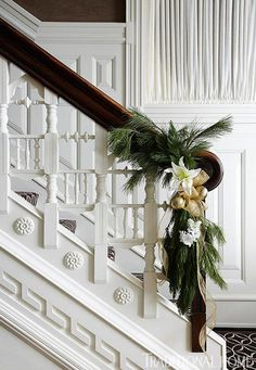 White tulips & gold ribbon really kick the holiday greenery up a notch. Unique stair rails. Traditional Home® / Photo: Werner Straube
