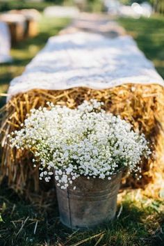hay bales with galvanized buckets of babies breath for the aisle and ceremony seating wedding