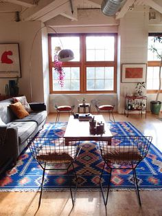Wood floors, bright fabrics, and industrial ceilings add layers of texture to this living room.