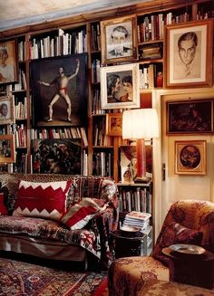 Very boho, wall of books, quirky framed pics, throws on sofa and chairs, layered rugs