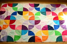 modern baby quilt  This is a classic quilt block called Drunkards Path. When the basic block is turned differently it can also make a Love Ring. Look up Drunkard's path. What makes this look so modern and fresh is the use of  Kona cotton solids with muslin.