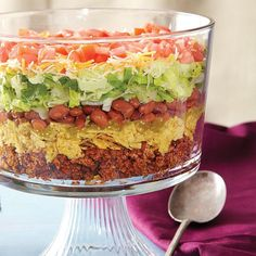 Recipe, grocery list, and nutrition info for Eight Layer Taco Salad. This gorgeous and colorful taco salad recipe is made healthier by using ground turkey in place of beef, adding Greek yogurt and bumping up the Taco Salad Recipes, Mexican Food Recipes, Vegetarian Mexican, Trifle Bowl Recipes, Taco Salad Doritos, Taco Salad Bowls, Trifle Dish, Trifle Recipe, Receita Trifle