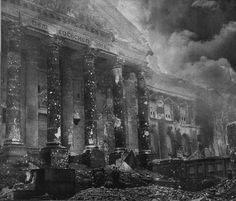 Reichstag burning. The end of Third Reich. Berlin 1945. At the bottom of the picture , in the middle, a small group of soldiers, most likely Russians, with a red flag.