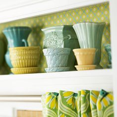 Vintage vases and planters. Love the matching paper that lines the shelf.