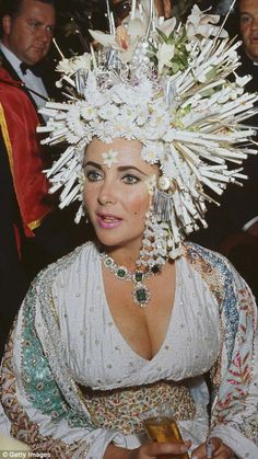 Elizabeth Taylor attends a social function wearing an elaborate headdress of pearls and artificial flowers, a jewelled dress and an emerald necklace. Bijoux D'elizabeth Taylor, Elizabeth Taylor Schmuck, Divas, Bijou Box, Violet Eyes, Emerald Necklace, Iconic Women, Grace Kelly, High Fashion
