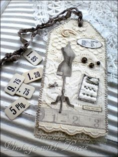 dressmaker tag with lace, buttons, safety pin, measuring tape ribbon... http://vintagewithlaces.blogspot.com/2011/07/tags.html#