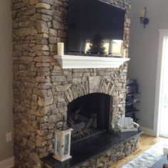stone fireplace, white mantel with TV