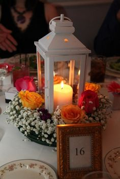 Lantern Wedding Centerpiece- set on a mirror with glass pebbles and rose petals scattered about.