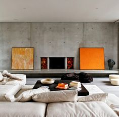 Exposed concrete walls juxtaposed with orange artwork....how simple and how lovely