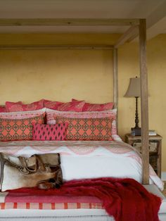 John Robshaw linens make up an oak four-poster in the basement's cozy guest quarters. #bedroom