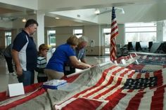 My Father, Brother and Nephew putting stitches in the World Trade Center flag in the cafeteria at Columbine.