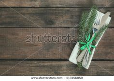 Country style christmas decoration with fir tree and green ribbon cutlery on old wooden brown background.